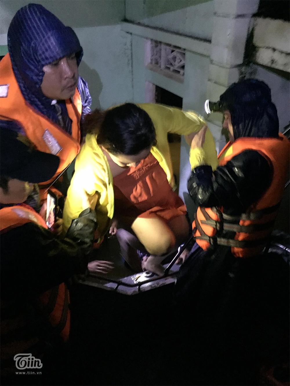 Mất điện do mưa lũ, các thành viên đội cứu hộ phải soiđèn pin để đưa chị Mến lên cano