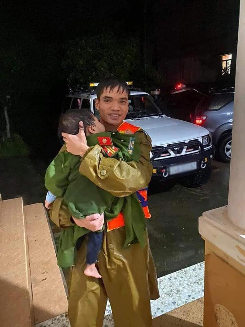 Người chiến sĩ cởi bộ quân phục còn khô ráo để ủ ấm cho cháu bé vừa được giải cứu. (Ảnh: Tiên Sa)