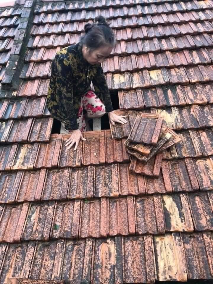 Một người phụ nữ dỡ ngói leo lên nóc nhà khi nước đã ngập sâu bên trong...