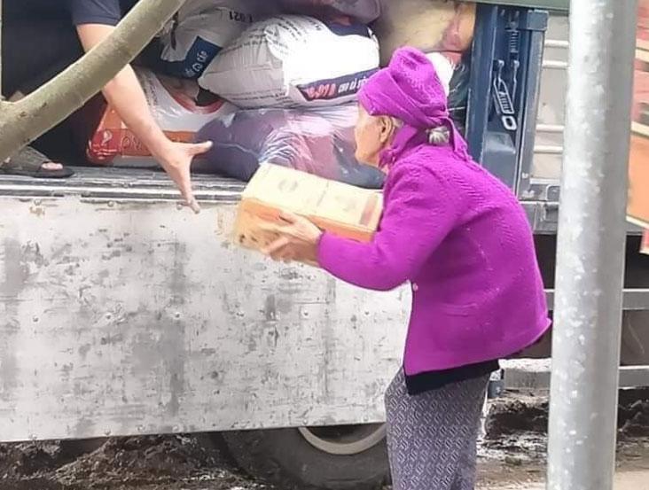 Cụ bà bê thùng mì để ủng hộ cho miền Trung.