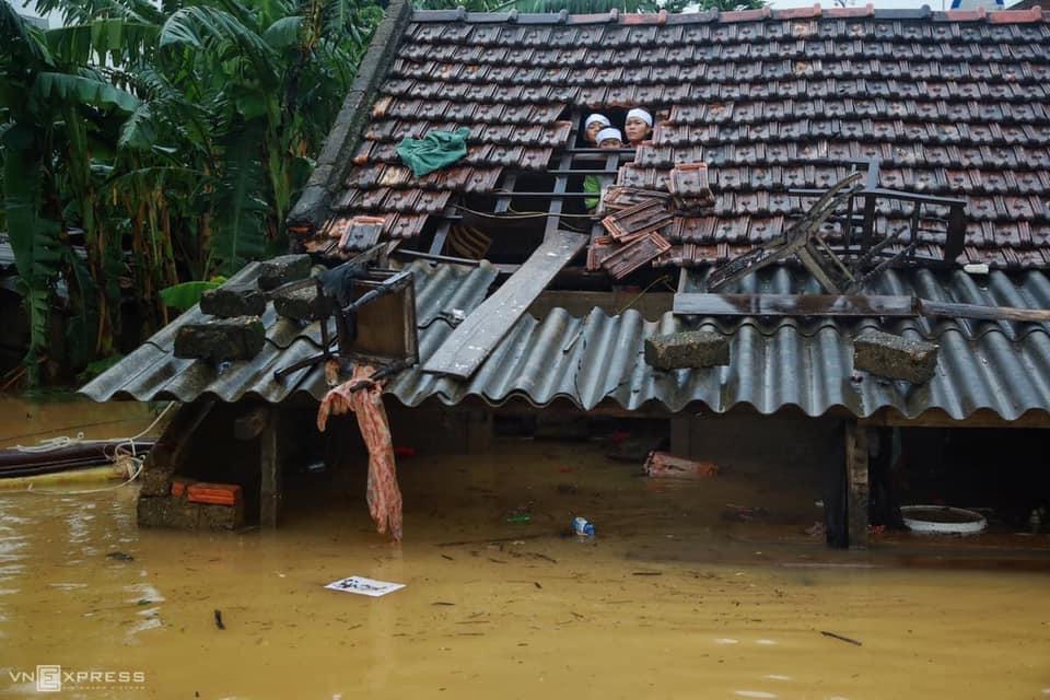 Mưa đã tạnh nhưng nước vẫn chưa rút, mọi thứ đều phải thông qua mái ngói như thế này. Ảnh: VnExpress.