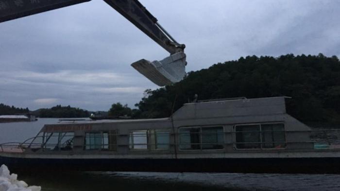Chiếc tàu được cẩu lên khỏi mặt nước lúc sáng sớm. Báo Giao thông.