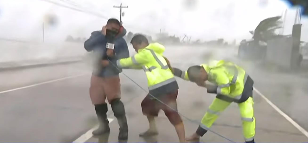 Lực lượng cứu hộ phải nương vào nhau vì gió quá mạnh.