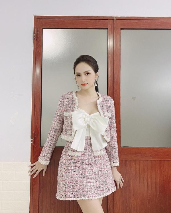 Hương Giang khoe nhan sắc kiều diễm ngọt ngàokhikhoác trên mình set đồ vải tweed màu hồng pastel pha chút tím đậm style cổ điển. Để tạo điểm nhấn cho set đồ, nàng Hậu sử dụng kiểu áo croptop trắng thắt nơ của Chanel mặc bên trong.