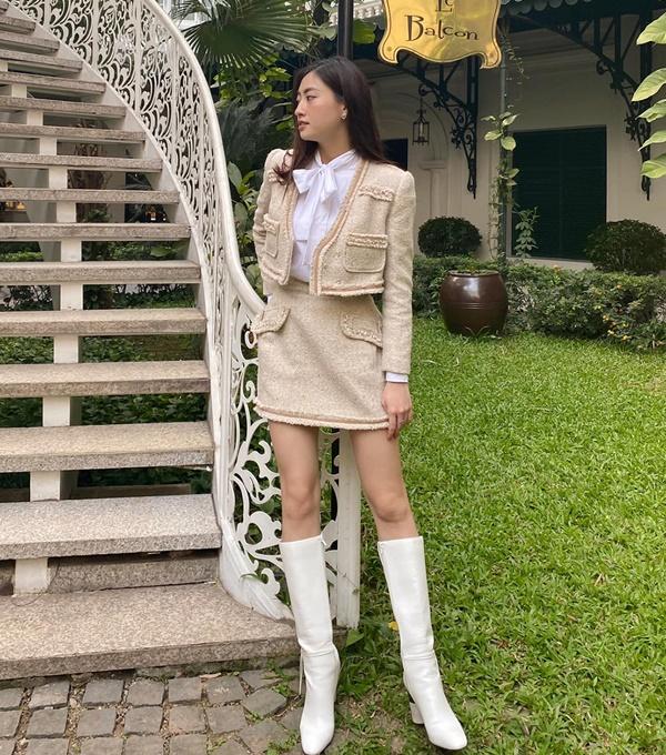 Ứng dụng cả cây đồ vải tweed màu sáng, Lương Thùy Linh xuất hiện với diện mạo sang chảnh và đẳng cấp. Nàng Hậu còn chọn thiết kế áo blouse thắt nơ và boots đùi trắng để tăng điểm nhấn cho cả set đồ đơn giản.
