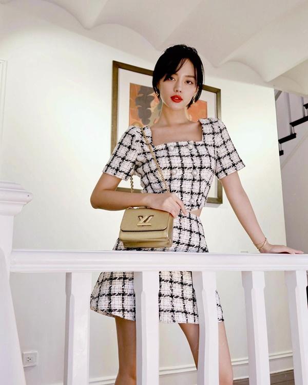 Khánh Linh cũng chọn diện cả set tweed mang sắc trắng đen cùng hoạ tiết caro cơ bản. Cô nàng còn khéo léo phối trang phục với túi Louis Vuitton màu ánh kim và vòng tay Cartier nhằm nâng tầm set đồ thêm đẳng cấp hơn.