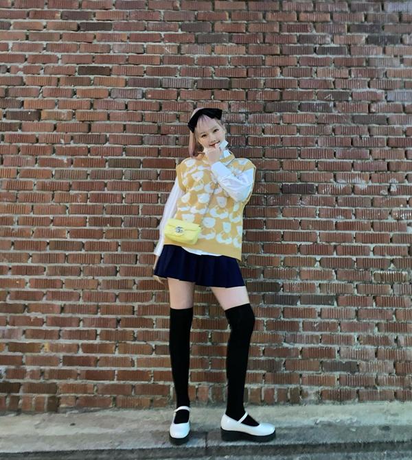 Sơ mi trắng, chân váy xếp ly ngắn, áo gile len màu sắc tươi sáng là combo giúp Yerin (Gfriend) có được set đồ trẻ trung, nữ tính. Loạt phụ kiện như cặp nơ, tất cao cổ và giày bệt càng khiến vẻ ngoài của cô nàng thêm duyên dáng nữ tính.