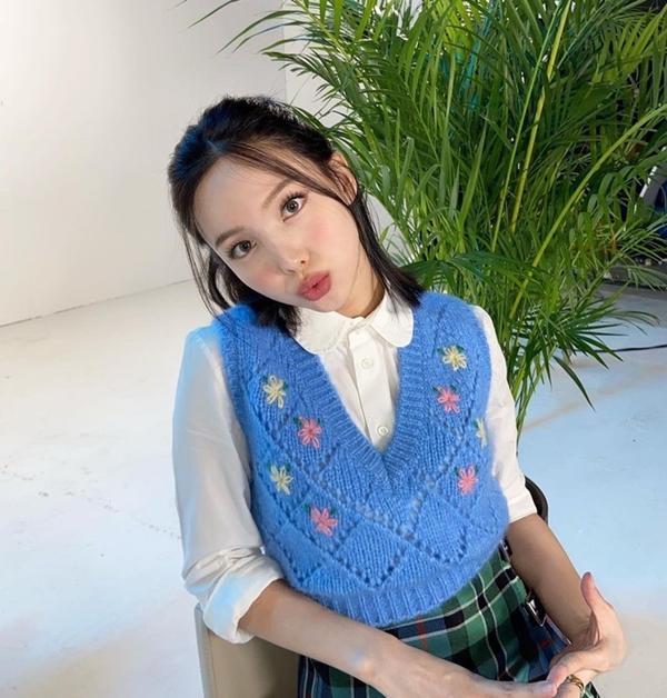 Nayeon (TWICE) lại mang đến công thức mới mẻ khi diện sơ mi trắng cổ lá sen với gile len màu xanh thêu hoa và chân váy kẻ trẻ trung.