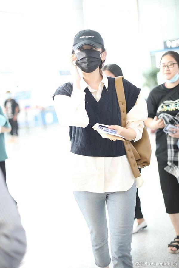 Dù đeo khẩu trang kín mít song Cổ Lực Na Trát vẫn thu hút sự chú ý tại sân bay. Cô nàng diện gile len lửng với sơ mi trắng và quần skinny jeans, đeo thêm túi xách da và đội mũ lưỡi trai cá tính.
