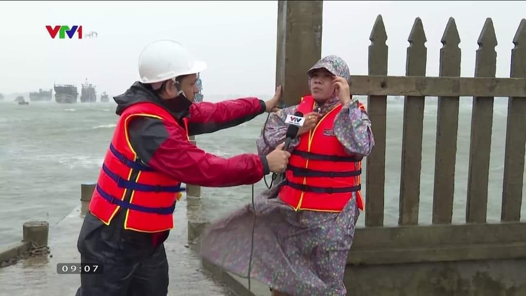 Hình ảnh phóng viên đứng ngay sát bờ biển, giữa cơn bão để tác nghiệp