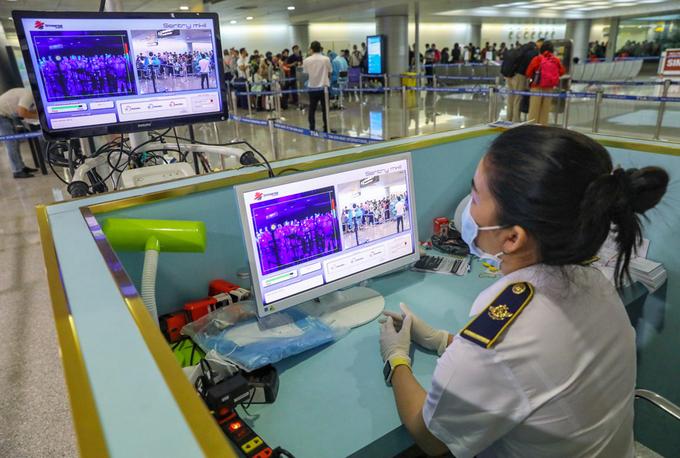 Nhân viên Trung tâm Kiểm dịch Y tế Quốc tế TP HCM (Sở Y tế) giám sát thân nhiệt người nhập cảnh tại sân bay Tân Sơn Nhất, ngày 24/3. Ảnh: Hữu Khoa.