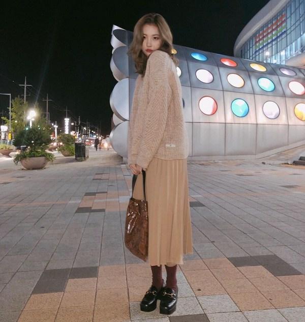 Với những cô nàng thích phong cách nữ tính, nhẹ nhàng thì đừng bỏ qua công thức đơn giản như của Sunmi với áo len màu be mix cùng chân váy xếp ly ton sur ton. Set đồ mùa lạnh ấm áp này sẽ sang xịn hơn nếu được hoàn thiện bằng một đôi giày mule thời thượng.