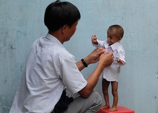 Thầy Cương chăm sóc từ ăn uống đến tắm giặt, thay quần áo, vệ sinh cá nhân của em (Ảnh: VnExpress.net)