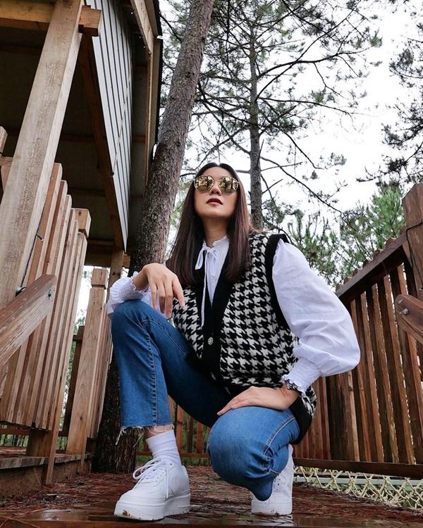 Set đồ gồm áo gile len họa tiết, quần jeans và sơ mi trắng của Thanh Hằng sẽ chẳng thể hoàn hảo nếu thiếu đi đôi sneakers trắng. Kiểu giày này giúp nữ siêu mẫu toát lên nét trẻ trung và năng động.