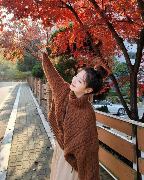 Kiểu áo len bện thừng tông nâu đất sẽ trẻ trung hơn nếu bạn layer với chân váy midi tông beige như Dahyun. Set đồ không khó phối và kén dáng là mấy mà lại còn rất hợp 'vibe' mùa thu.