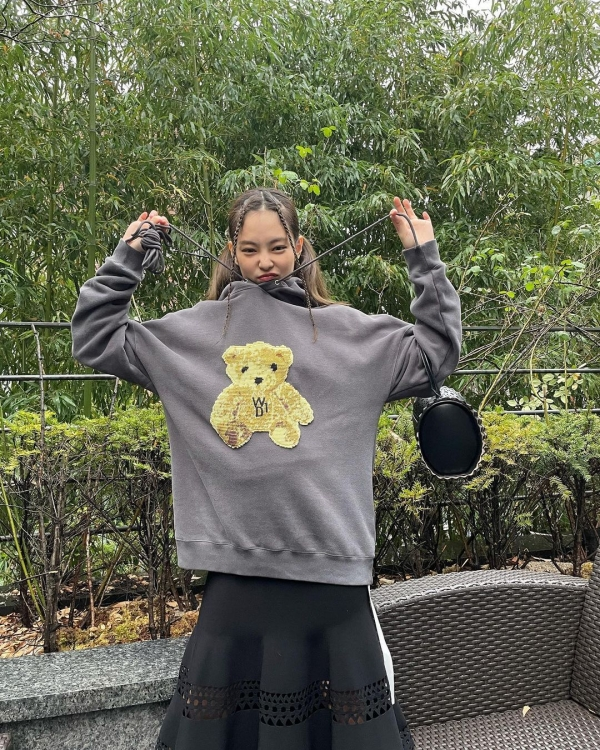 Jennie có 1 pha mix đồ gây tranh cãi giữa hoodie in hình chú gấu giữa áo và chân váy midi. Theo lẽ thường thì cách mix&match này tạo cảm giác 'trái ngang', nhưng vì Jennie chọn phối tông xám và đen rất hòa hợp nên tổng thể mang đến cảm giác cá tính và độc lạ nhiều hơn.