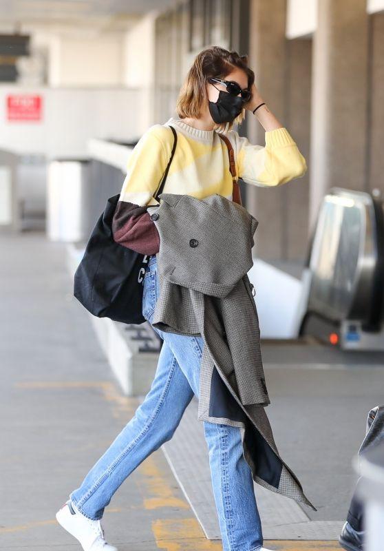 Kaia Gerber lộ diện tại sân bay trong set đồ đơn giản, mix từ sweater len sáng màu và quần jeans ống đứng.