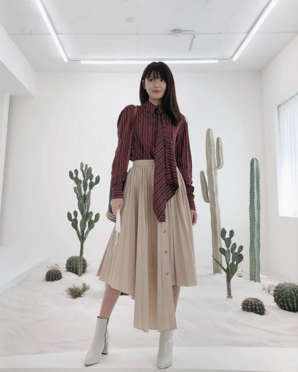 Với những quý cô yêu thích phong cách trưởng thành, kiểu blouse màu đỏ rượu với thiết kế cà vạt phối cùng chân váy bất đối xứng màu trà sữa như Sooyoung cũng đáng để tham khảo.