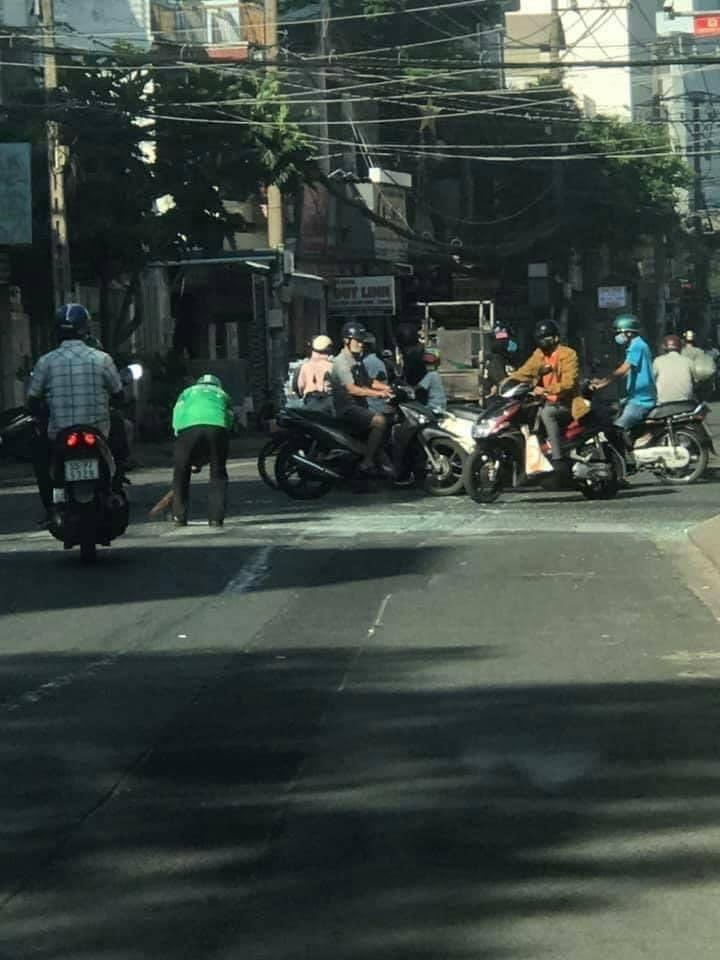 Tài xế xe ômquét sạch đường sau khi xảy ra tai nạn giao thông. Ảnh H.V.C.