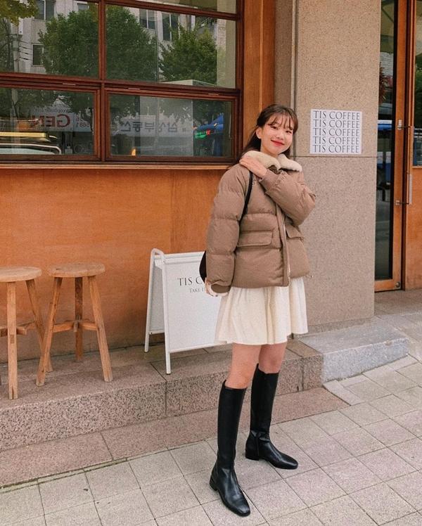 Áo phao dáng ngắn là item không thể thiếu của gái Hàn, nhất là vào mùa lạnh. Nhưng cô bạn này còn thể hiện sự sáng tạo hơn nữa khi khoác item này bên ngoài váy xòe và mix cùng boots da cao ngang gối thời thượng.