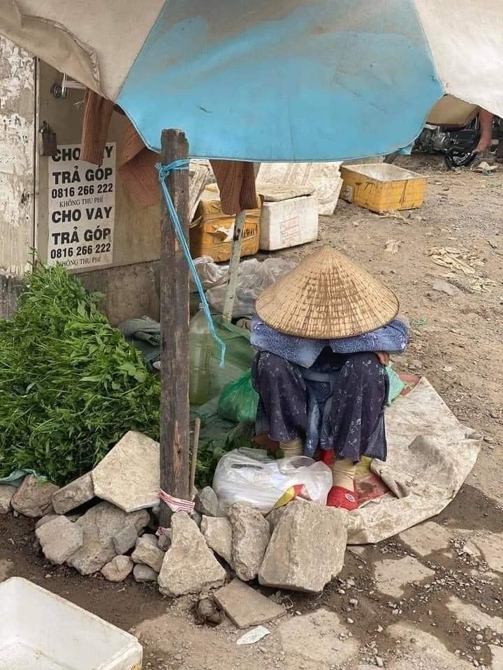 Giữa thành phố rộng lớn, cụ bà bán rau lang nhỏ bé và lạc lõng bên một góc đường. Ảnh Phạm Minh Khương.