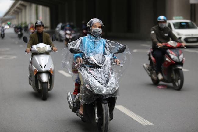 Dù thời tiết khô ráo, nhiều người vẫn mặc áo mưa để tránh gió lạnh.
