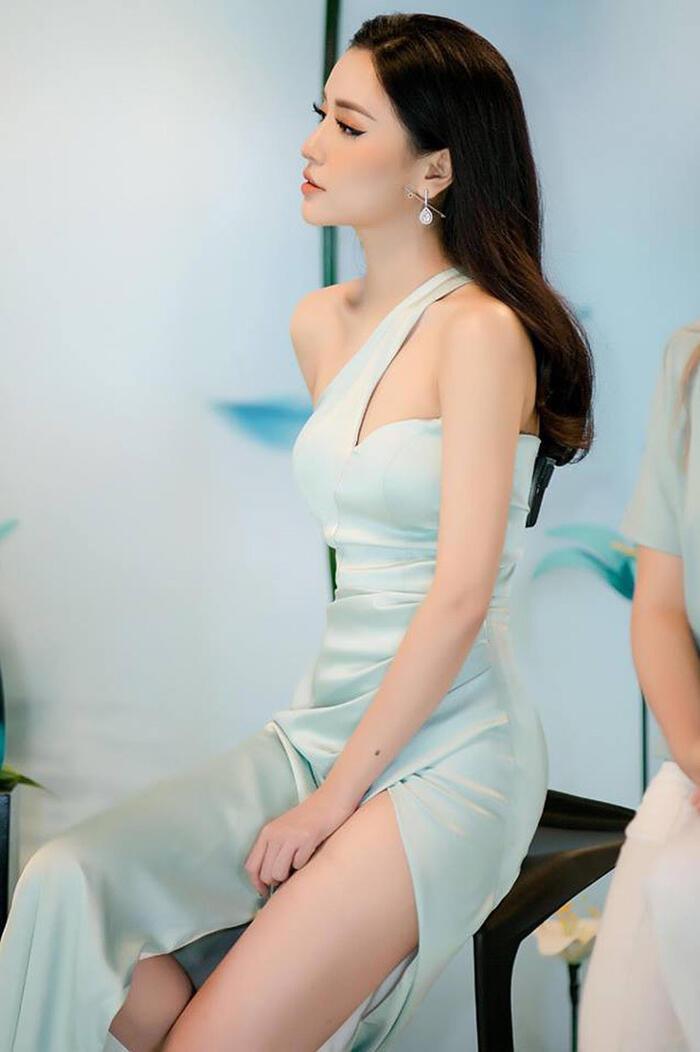 Bích Phương vén váy che đùi, tay còn lại cẩn thận phủ lên đầm tránh những góc nhìn không hay.