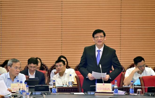 Quyền Bộ trưởng Bộ Y tế Nguyễn Thanh Long trình bày Tờ trình tại phiên họp.