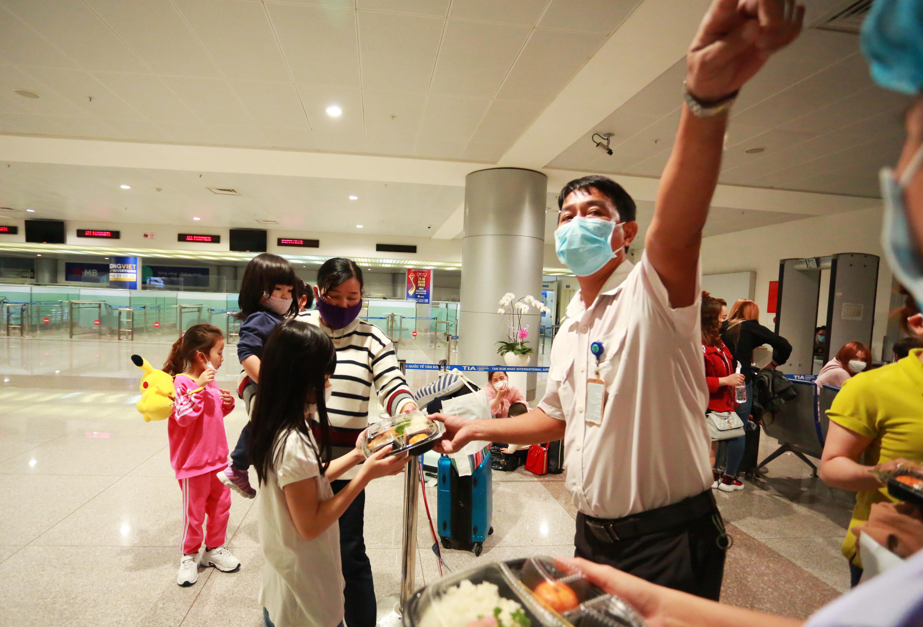 Nhân viên Trung tâm kiểm dịch y tế Quốc tế phát cơm cho các hành khách trong lúc chờ được đưa đi cách ly.