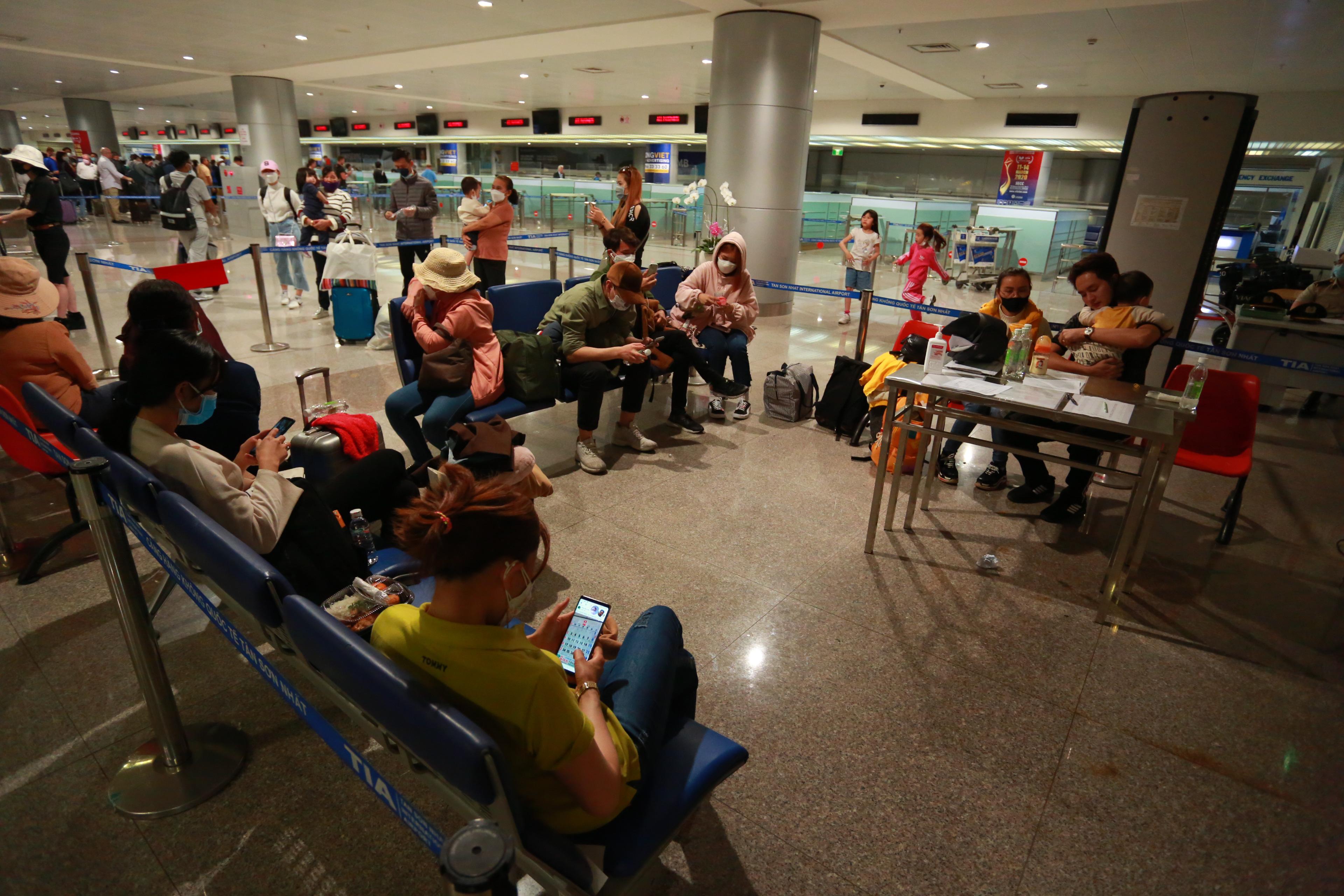 Một đoàn khách khoảng 20 người gồm cả người Việt Nam và Hàn Quốc đang chờ để di chuyển đến cơ sở y tế để cách ly, sau khi từ Hàn Quốc về sân bay Tân Sơn Nhất.