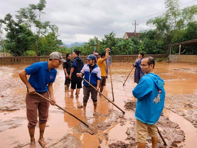 Thầy, trò, phụ huynh cùng nhau dọn dẹp bùn, rác thải trường học để sớm trở lại học tập.