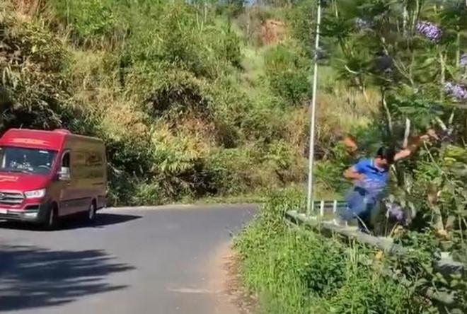 Cảnh ông T. rời khỏi xe để bẻ hoa phượng tím bên đường. Ảnh cắt từ clip