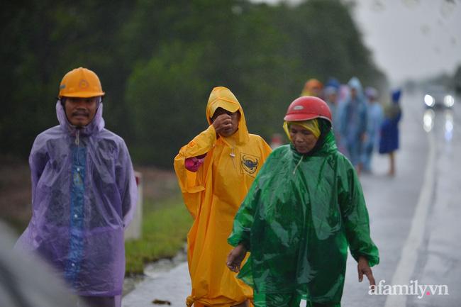 Mặc dù trời mưa rất to và lạnh nhưng người dân vẫn dầm mình đứng đợi 2 bên dọc theo tuyến đường tránh.