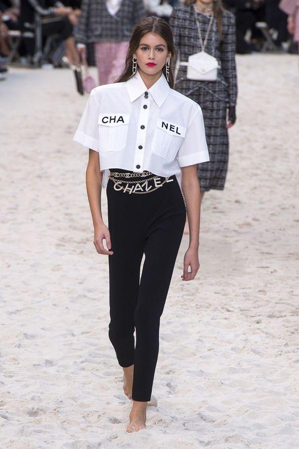 Set đồ áo sơ mi croptop mix cùng quần đen dài nhấn nhá chiếc thắt lưng xiềng xích lấp lánh thuộc BST Chanel Xuân - Hè 2019 được chân dài Kaia Gerber khoác trên mình sải bước trên sàn runway hồi năm 2018.