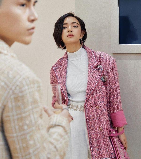 Set đồ thanh lịch đến từ Fashionista Việt Châu Bùi trong một lần cô tham show thời trang của nhà mốt Pháp tại nước ngoài, điểm nhấn của phụ kiện đã làm tôn lên set đồ trắng bên trong mix cùng áo khoác vải tweed màu hồng rực rỡ.