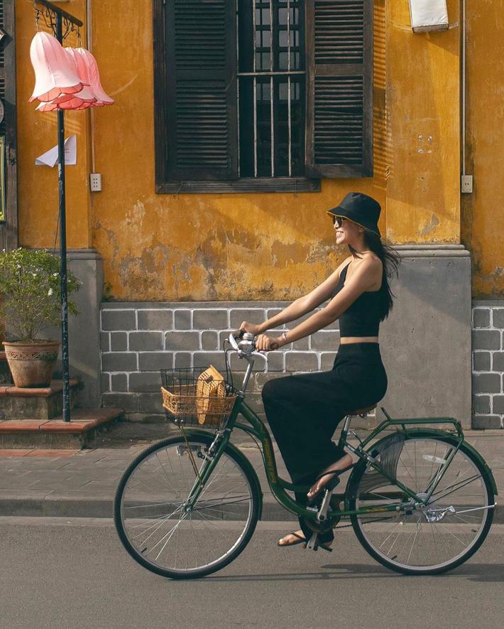 Hoa hậu Tiểu Vy tự tin khoe vòng eo con kiến thắt chặt với nguyên set đồ đen tung tăng đạp xe dạo phố cổ Hội An.