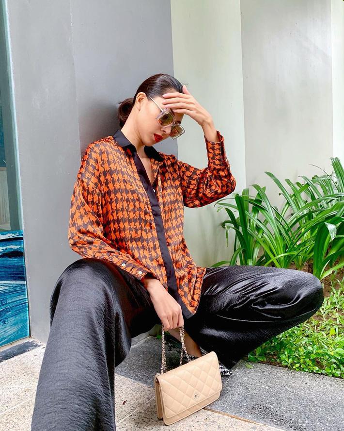 Quần lụa bóng tưởng là style của các bà các mẹ ngày xưa lại được Minh Triệu mix&match chất lừ với sơmi họa tiết cùng túi xách Chanel sang chảnh.