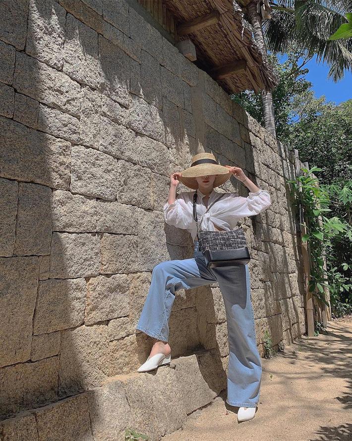 Tóc Tiên chinh phục mốt quần jeans ống thụng bằng cách mix cùng sơmi trắng buộc vạt.