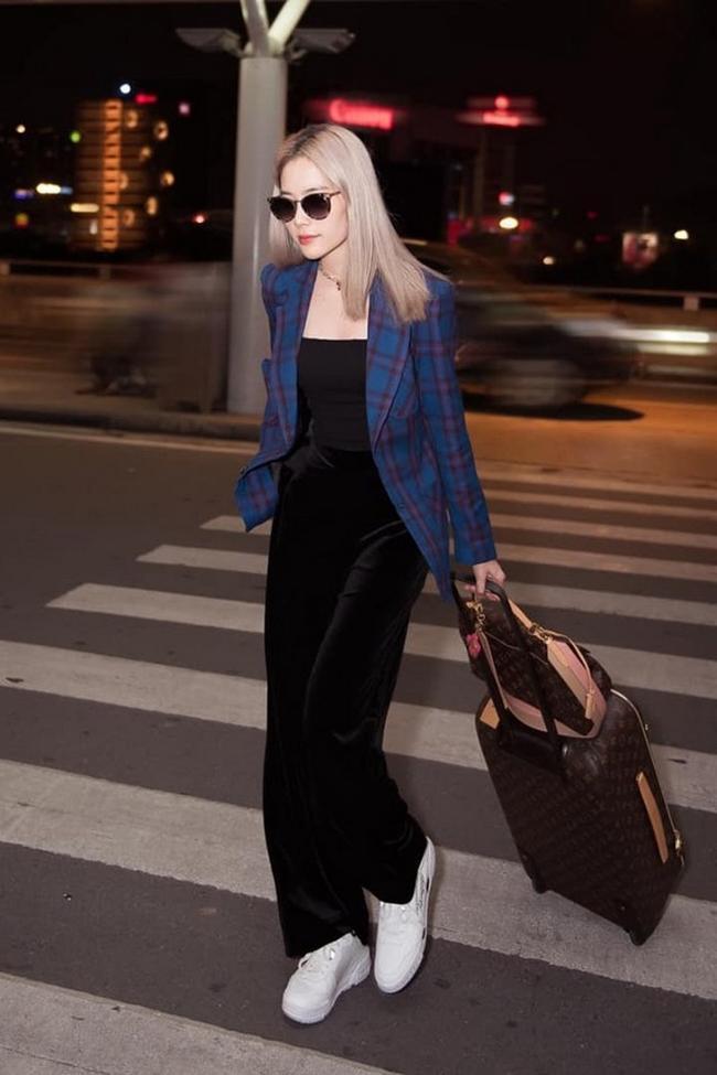Nam Em xuất hiện ở sân bay với set đồ màu đen khoác thêm ngoài áo blazer kẻ caro màu xanh nổi bật. Set đồ tôn lên làn da trắng mịn cho người đẹp. Để có vẻ ngoài ấn tượng, Nam Em còn mix thêm phụ kiện đắt đỏ là túi xách và vali của thương hiệu Louis Vuitton. Được biết, tổng giá trị của 2 món đồ hiệu này lên tới hơn 100 triệu đồng.