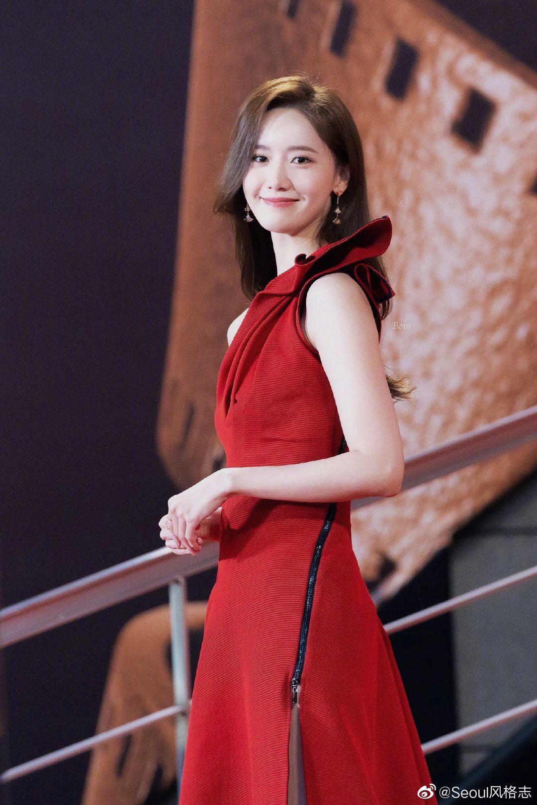 Sau đó Yoona đổi sang mẫu váy đỏ lệch vai kiểu cách. Sắc đỏ nổi bật tôn lên nước da trắng sáng, xương quai xanh thanh mảnh. Cùng với đó cô cũng chuyển sang kiểu tóc buông xõa, uốn xoăn nhẹ nhàng đúng chuẩn nữ thần.