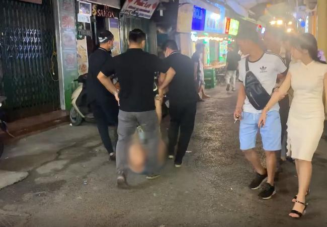 Nhân viên quán bar kéo người phụ nũ ra ngoài khu vực quán. Ảnh cắt từ clip.