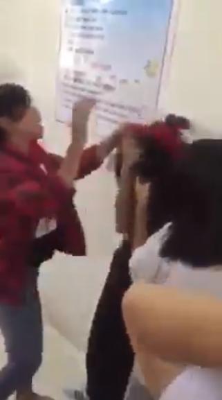 Nhóm nữ sinh còn đeo khăn quàng đỏ đánh, tát tới tấp vào người vào mặt nữ sinh áo đen. Ảnh cắt từ clip