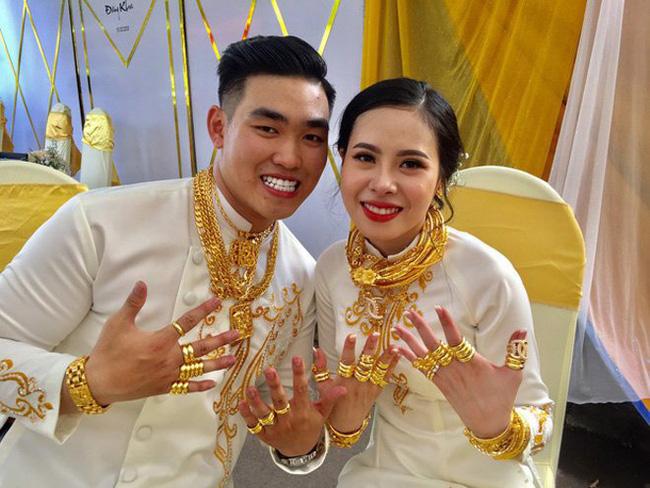 Cặp đôi cô dâu chú rể với số của hồi môn toàn vàng trên người.