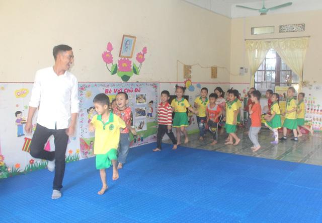 Thầy Hùng đang vui đùa với các bé trong giờ học vận động