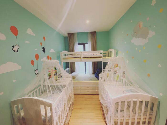 Căn phòng có tông màu xanh pastel chủ đạo được trang bị 2 chiếc nôi gắn nhiều hình con thú cùng với đó là giường 2 tầng màu trắng vô cùng xinh