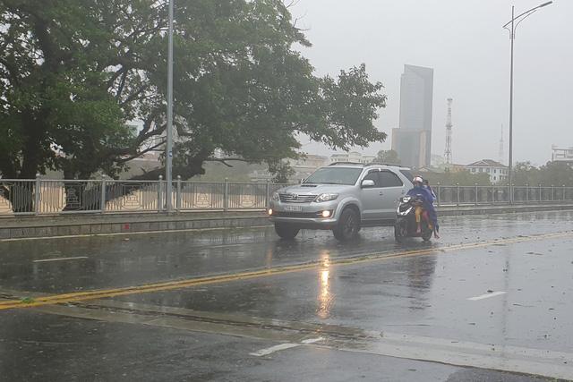 Một chiếc ô tô dìu một phụ nữ với 2 cháu nhỏ đi qua cầu.