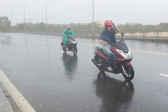 Người dân gặp khó khăn do gió lớn khi di chuyển qua cầu Phú Xuân.