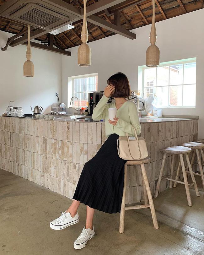 Chân váy xếp ly đen + áo cardigan + giày sneaker trắng là bộ 3 đơn giản nhưng được đánh giá cực cao ở độ trendy, thanh lịch.