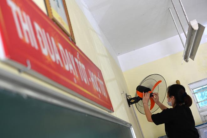Một giáo viên lau chùi, kiểm tra lại quạt điện lắp đặt xung quanh lớp học. Khi học sinh trở lại lớp học cũng là khi vào hè, những chiếc quạt máy sẽ vô cùng ý nghĩa giúp các em tập trung theo dõi bài học hơn giữa nắng nóng của mùa hè.