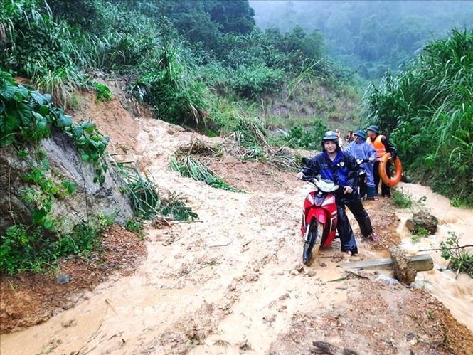 Người dân rất khó khăn và gặp nhiều nguy hiểm khi qua lại các tuyến đường bị sạt lở do mưa lũ tại tỉnh Quảng Bình. Ảnh: TTXVN phát